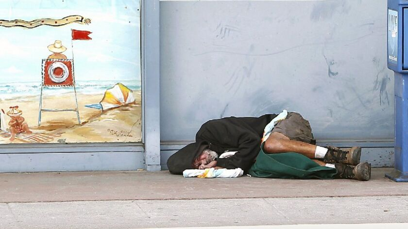 A homeless man sleeps on the curb at Mountain and south coast highway in Laguna.(Photo by David Hans