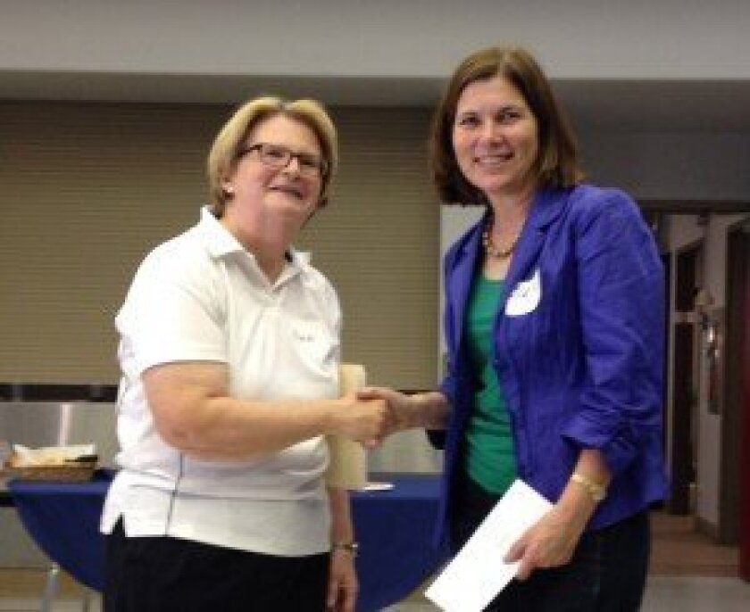 Friends President Ann Welton presents scholarship winner Clare White McDonald with a check for $500 at the annual Friends Volunteer luncheon.