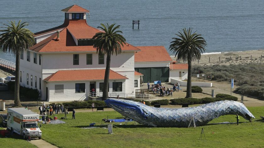 Artist Joel Deal Stockdill, lower right, works on a blue whale art piece made from discarded single-