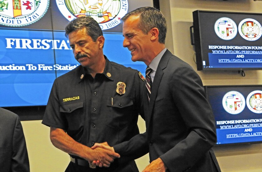 L.A. Fire Chief Ralph Terrazas, left, shakes hands with Mayor Eric Garcetti after a press conference to announce the launch of FireStat LA, a new database to gauge the department's performance. Statistics show response times to 911 calls have slowed this year.