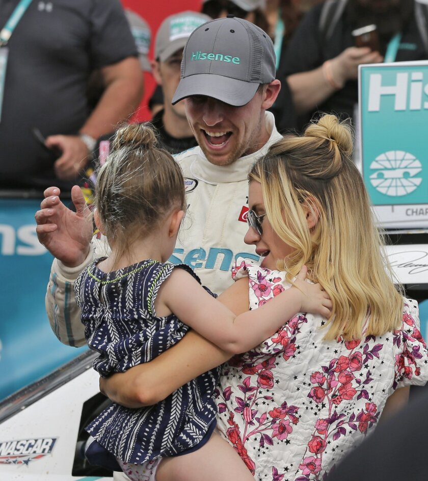 Denny Hamlin, center, celebrates in Victory Lane with his girlfriend Jordan Fish, right, and their daughter Taylor James Hamlin, left, after winning the NASCAR Xfinity series auto race at Charlotte Motor Speedway in Concord, N.C., Saturday, May 28, 2016. (AP Photo/Chuck Burton)