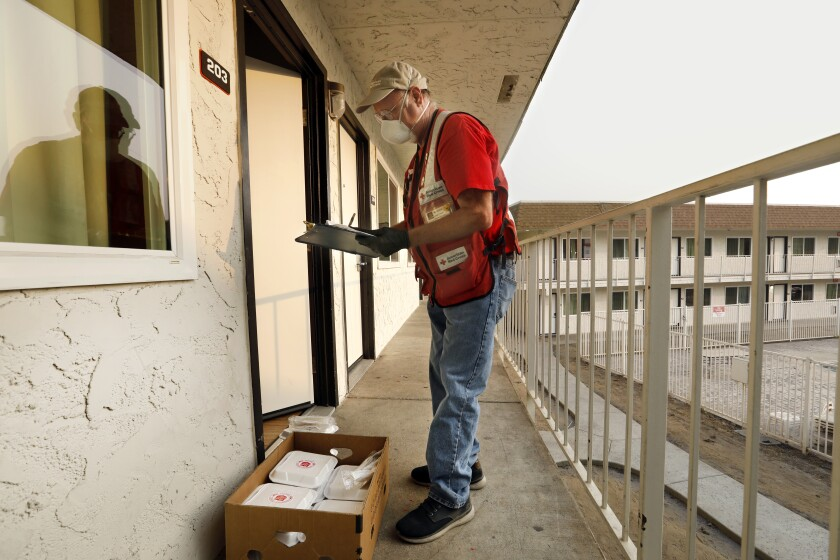 Red Cross volunteer wearing a mask and reflective vest stands outside a motel door with a clipboard and box of packaged meals
