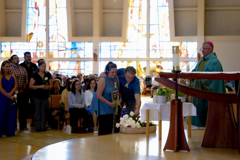 Cecilia and David Bradley of Poway place a white rose on the altar for their son, Ryan, during the Mass for Survivors of Suicide Loss Sunday at Our Mother of Confidence Catholic Church in University City. The Rev. John P. Dolan, auxiliary bishop of the Roman Catholic Diocese of San Diego, pictured at right, presided over the event which saw 75 white roses placed in memorial of loved ones lost.