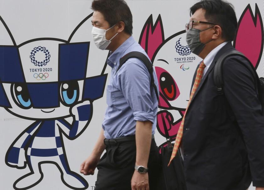 Dos personas caminan por delante de un cartel promocional de los Juegos Olímpicos, en Tokio