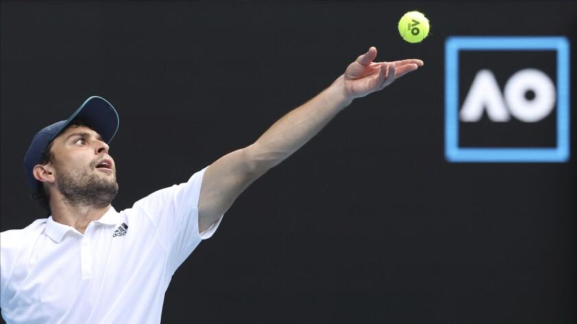 Russia's Aslan Karatsev serves to Bulgaria's Grigor Dimitrov during their quarterfinal match at the Australian Open tennis championship in Melbourne, Australia, Tuesday, Feb. 16, 2021.(AP Photo/Hamish Blair)