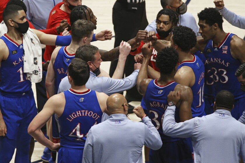 Kansas coach Bill Self meets with players during the second half of an NCAA college basketball game against West Virginia, Saturday, Feb. 6, 2021, in Morgantown, W.Va. (AP Photo/Kathleen Batten)
