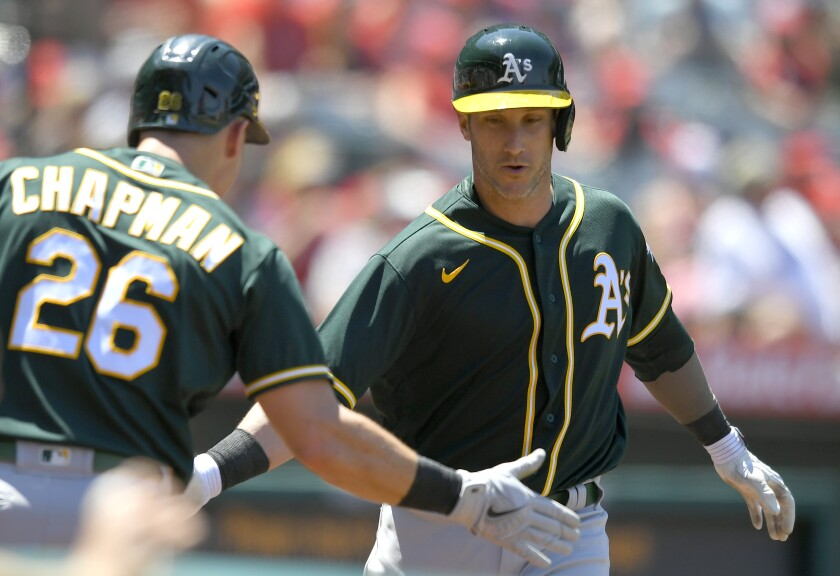 Oakland Athletics' Matt Chapman, left, congratulates Yan Gomes on his two-run home run in the fourth inning while playing against the Los Angeles Angels in a baseball game Sunday, Aug. 1, 2021, in Anaheim, Calif. (AP Photo/John McCoy)