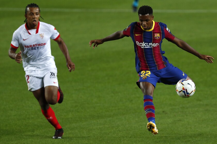 Barcelona's Ansu Fati fights for the ball against Sevilla's Franco Vazquez during the Spanish La Liga soccer match between FC Barcelona and Sevilla FC at the Camp Nou stadium in Barcelona, Spain, Sunday, Oct. 4, 2020. (AP Photo/Joan Monfort)