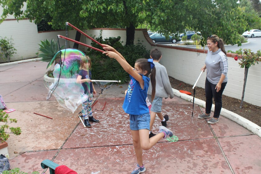 Kids make bubbles on the library patio.