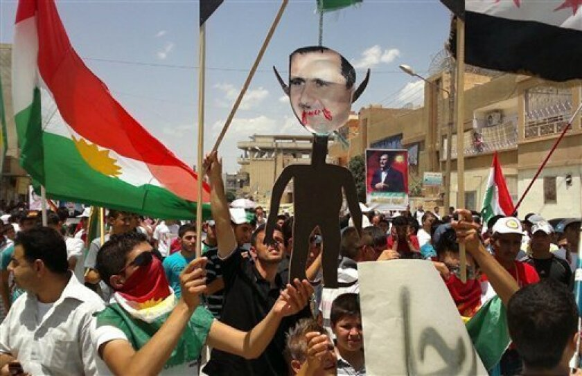 """FILE - This Friday, June 15, 2012 file citizen journalism image provided by Shaam News Network SNN purports to show anti-Syrian regime Kurdish protesters holding an effigy of Syrian President Bashar Assad as they wave their Kurdish flag during a demonstration called the """"Friday of Russia is the enemy of Syrian people,"""" at the northeastern town of Amouda, Syria. (AP Photo/Shaam News Network, SNN, File )THE ASSOCIATED PRESS IS UNABLE TO INDEPENDENTLY VERIFY THE AUTHENTICITY, CONTENT, LOCATION OR DATE OF THIS HANDOUT PHOTO"""