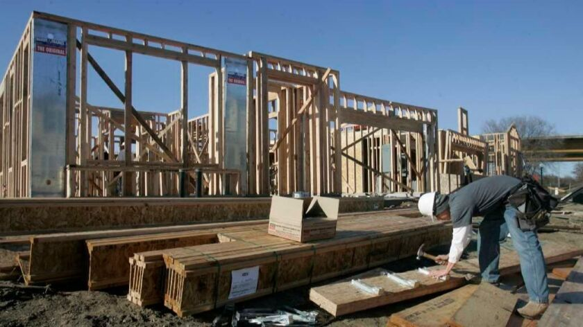 A worker builds a home in Sacramento. A new state report says California's housing crisis will continue until public support grows for making it easier to add housing stock.
