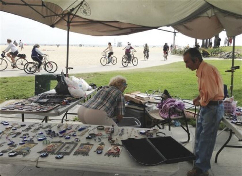 Mustafa, right, and his wife, Yesim Balci work at their stand along the Venice, Calif., beach boardwalk Sunday Aug. 4, 2013 near where a Saturday incident involving a driver who accelerated through a crowd of beachgoers, hitting one person after another as bystanders tried desperately to get out of the way. The hit-and-run killed an Italian woman on her honeymoon and hurt 11 others. (AP Photo/Tami Abdollah)