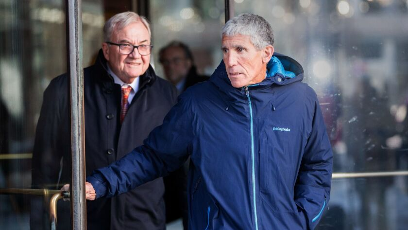 "William ""Rick"" Singer, right, the admitted ringleader of an immense academic fraud, leaves federal court in Boston on Tuesday."