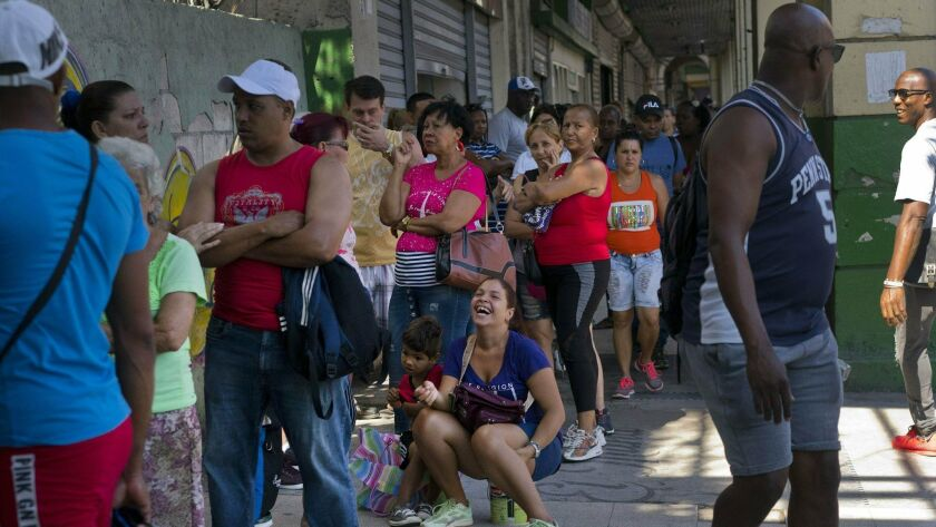 People wait in line to buy chicken at a government-run grocery store in Havana, Cuba, Wednesday, Apr
