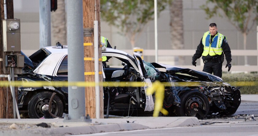 Ontario police officers look over the smashed vehicle which broadsided a San Bernardino Police Department squad car, killing officer Bryce Hanes early Thursday morning, Nov. 5, 2015, in Ontario, Calif.