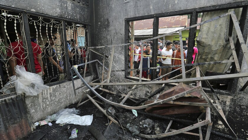 Residents examine the damage after a fire razed through a match factory in Langkat, North Sumatra, I