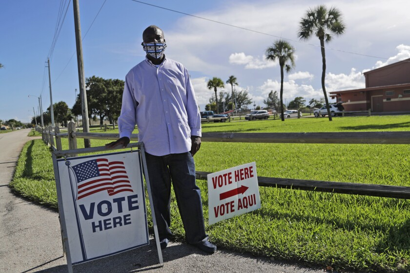 """William Freeman, 51, poses near """"Vote here"""" signs outside his polling station in Riviera Beach, Florida"""