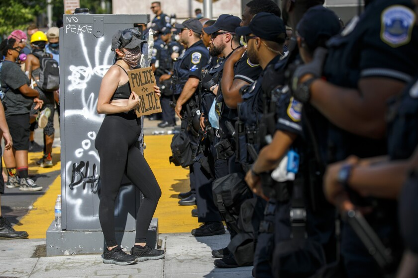 """A woman holds up a sign saying """"police the police"""" as she confronts a police line"""