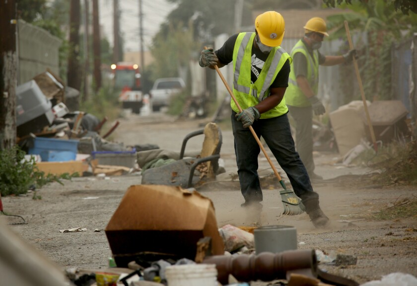 Los Angeles sanitation workers Erik Scott, left, and Cesar Galvez clean up an alley behind the 700 block of East 107th Street.