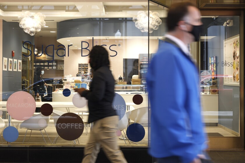 People walk past Sugar Bliss Bakery in Chicago's famed Loop on Tuesday, May 4, 2021. In many downtown areas where companies closed their offices and commuting ground to a halt, sandwich shops, bakeries and other small businesses are waiting with guarded optimism for their customers to return. (AP Photo/Shafkat Anowar)