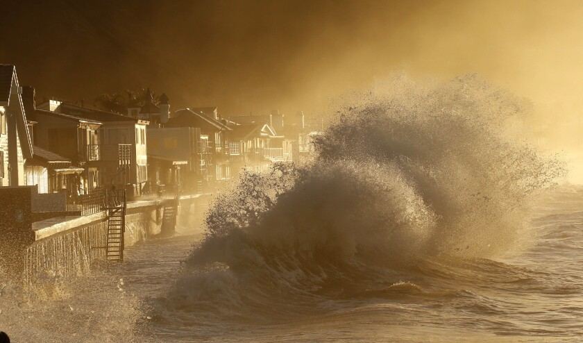As the suns rises ove the Solimar burn area west of Ventura,heavy surf slams the homes at Mondo's Beach between the Solimar and Faria Beach communities Thursday morning.