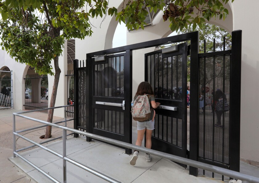 At the end of the school day at L.R. Green Elementary School a student exits one of the heavy steel gates protecting the school.