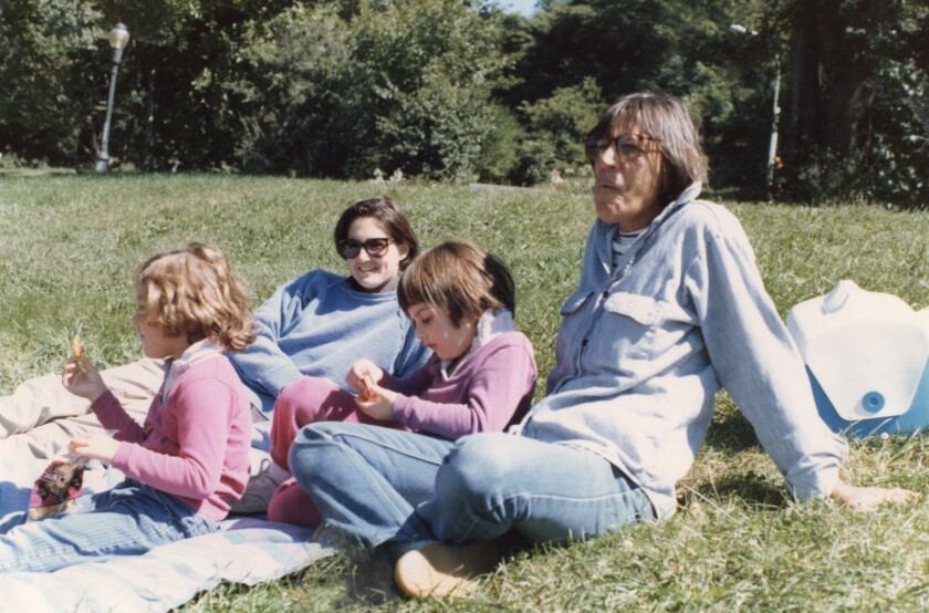 Two moms sit having a picnic in the grass with their toddler daughters in a family photograph