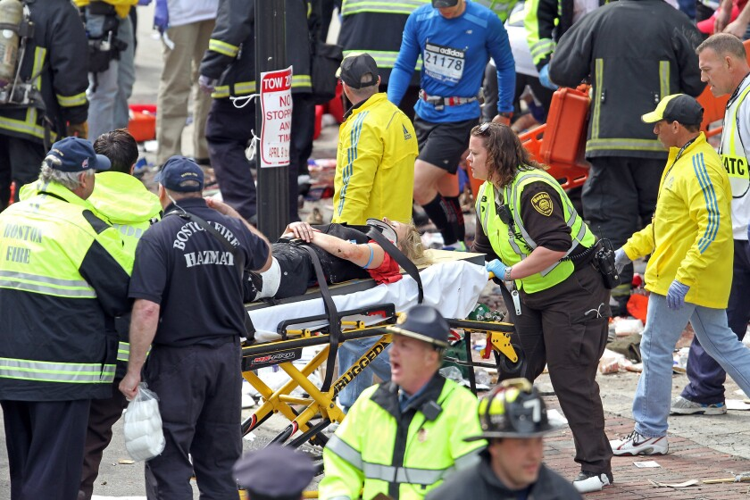 Rescue personnel aid injured people near the finish line of the 2013 Boston Marathon following explosions.
