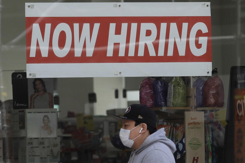 A file photo shows a man wearing a mask while walking under a Now Hiring sign.