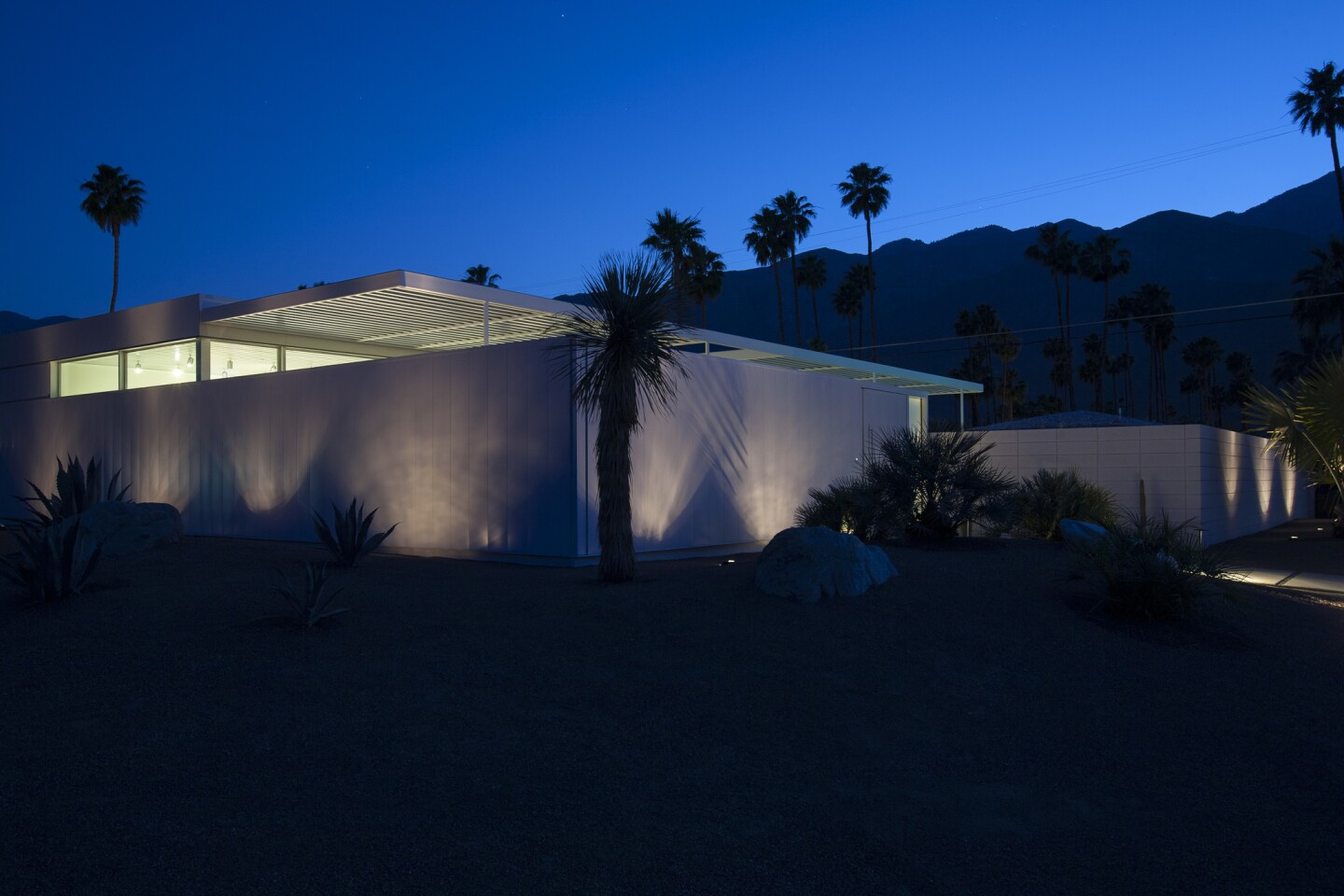 The white walls of Desert Two glow under the silhouettes of palm trees and the San Jacinto Mountains. Developer and project manager Dave McAdam said the house sits on what had been the last empty lot in the Deepwell neighborhood of Palm Springs.
