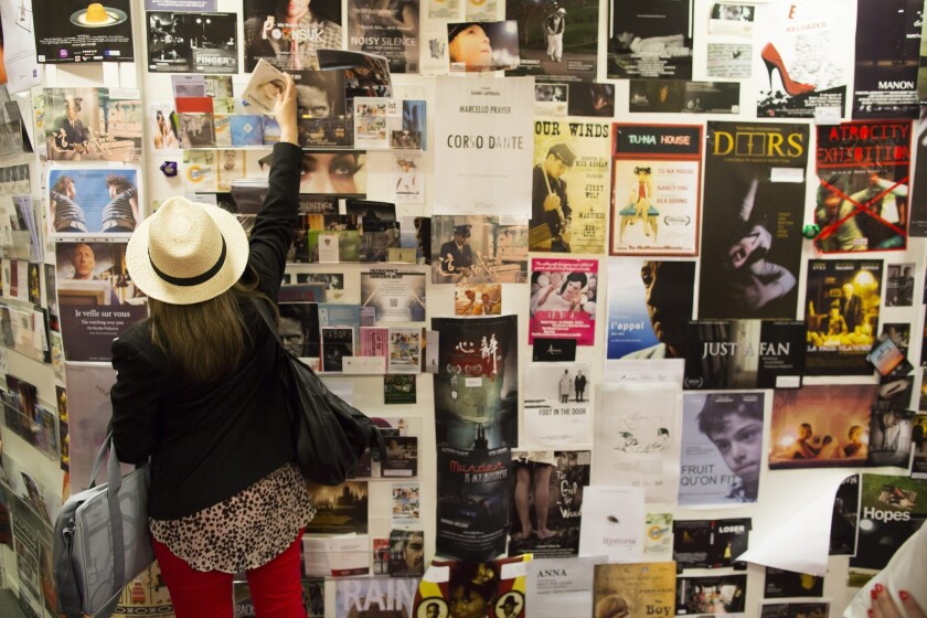 Movie posters are displayed on a wall at the film market at the 66th Cannes Film Festival.