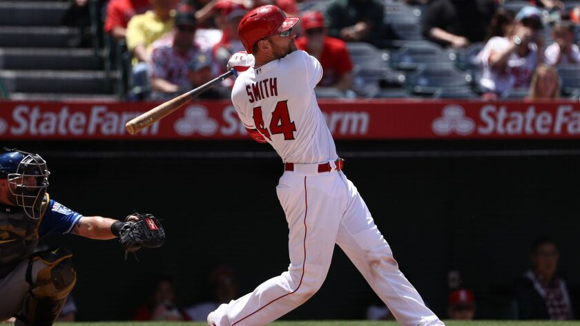 Angels catcher Kevan Smith hits an RBI double in the fourth inning against the Kansas City Royals at Angel Stadium on Sunday.