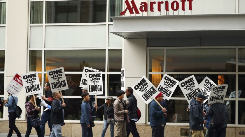 FILE - In this Oct. 4, 2018 file photo, hotel workers strike in front of a Marriott hotel in San Fra