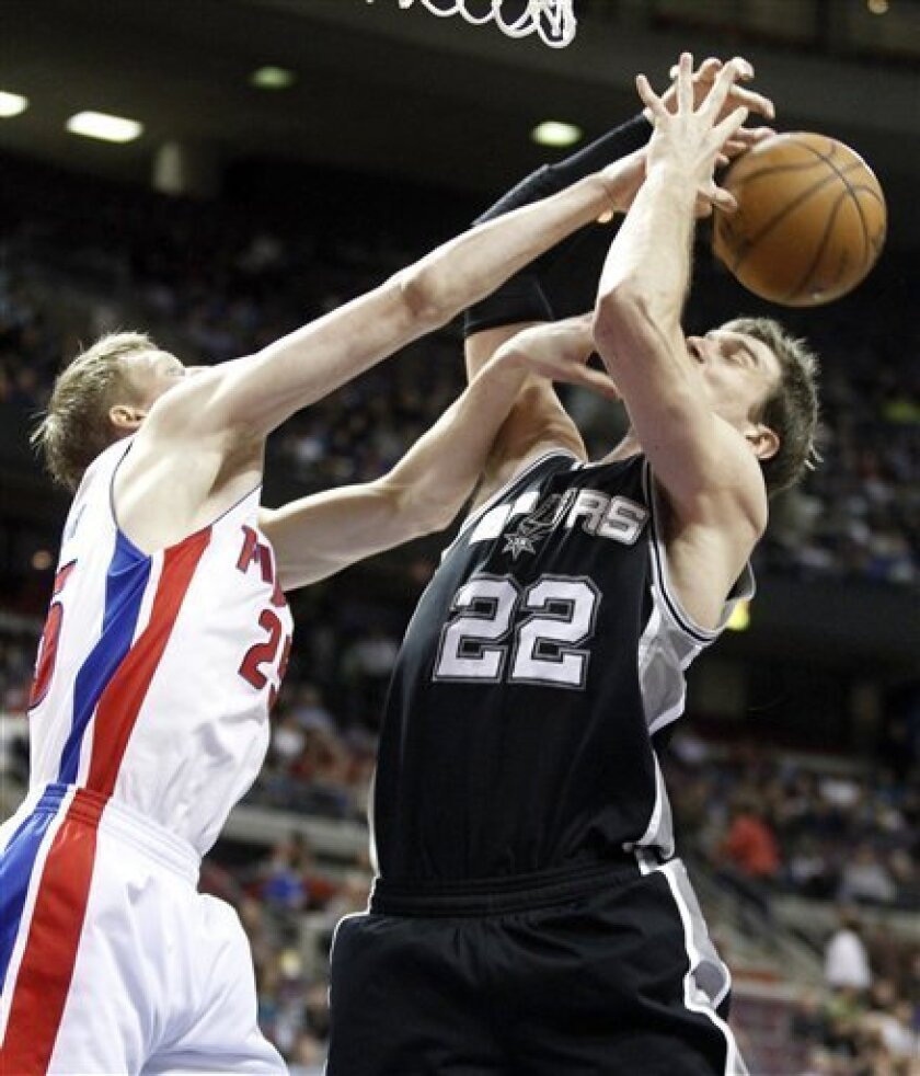Detroit Pistons forward Kyle Singler, left, knocks a rebound away from San Antonio Spurs center Tiago Splitter (22) in the second half of an NBA basketball game Friday, Feb. 8, 2013, in Auburn Hills, Mich. The Pistons defeated the Spurs 119-109. (AP Photo/Duane Burleson)
