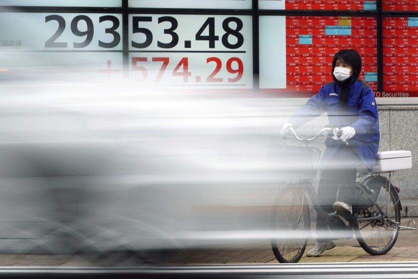 A woman wearing a protective mask rides a bicycle in front of an electronic stock board showing Japan's Nikkei 225 index at a securities firm Monday, Feb. 8, 2021, in Tokyo. Asian shares mostly rose Monday, tracking a rally on Wall Street last week, with Japan's benchmark momentarily reaching three-decade highs, on growing optimism about the global economy. (AP Photo/Eugene Hoshiko)