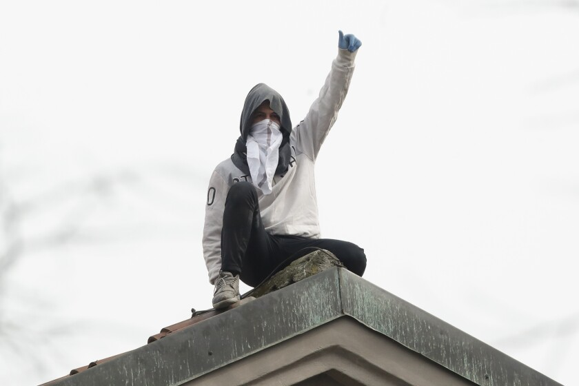A man gestures from the roof of San Vittore prison in Milan, Italy, during an inmate protest Monday.
