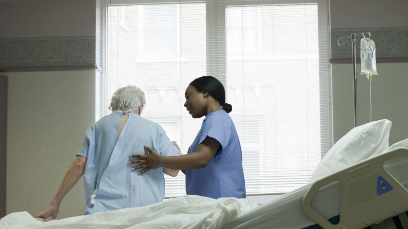 AA woman nurse helping patient stand up