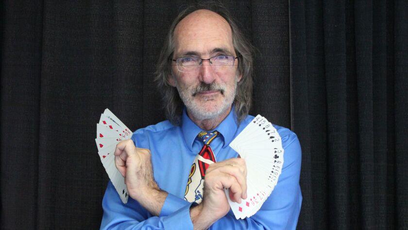 Bridge teacher and magician Scott Farr performs a card trick.