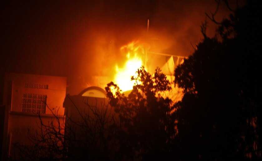 Flames engulf the Ambassador Hotel as fighting continues into the night, following a bomb attack on the hotel in Mogadishu, Somalia, Wednesday, June 1, 2016. Somalia's Islamic extremist rebels al-Shabab stormed the hotel killing people and taking a number of hostages, police said. (AP Photo/Farah A