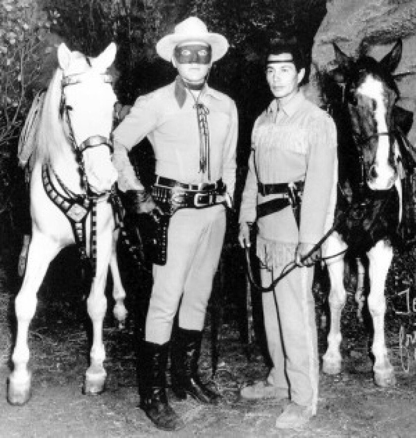 """John Hart temporarily replaced Clayton Moore as the Masked Man on the """"The Lone Ranger"""" television series beginning in 1952. With him are Jay Silverheels as Tonto and their horses, Silver and Scout."""
