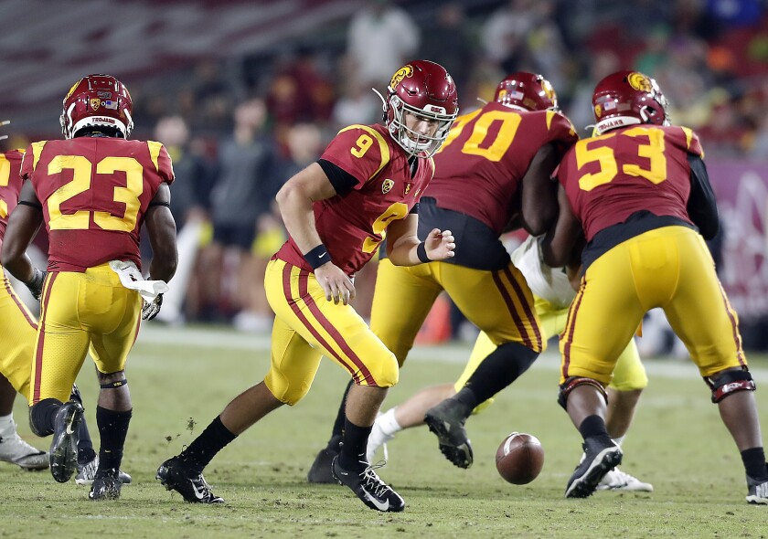 USC quarterback Kedon Slovis chases after a fumbled snap against Oregon in the fourth quarter at the Coliseum on Saturday.