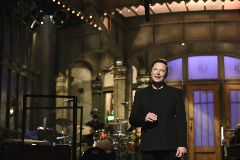 """Elon Musk smiles on the """"SNL"""" stage."""