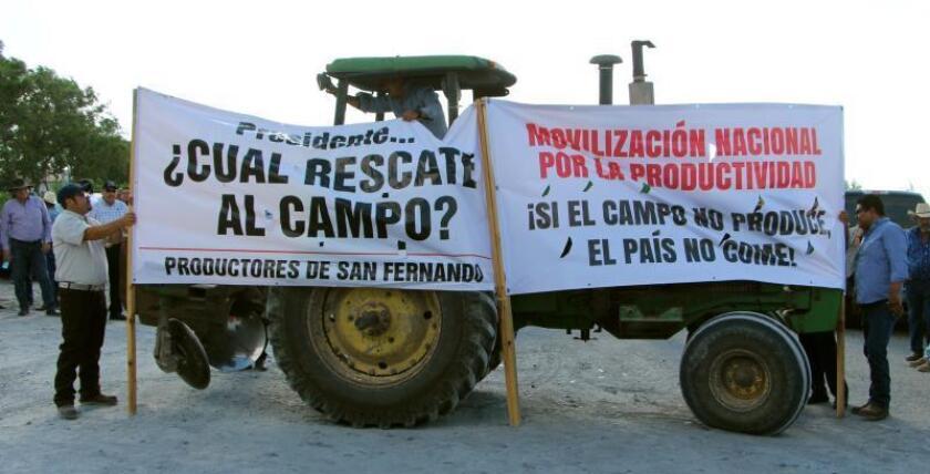 Agricultores bloquean este miércoles la vía que conduce al poblado de Nuevo Progreso, Río Bravo, en el estado de Tamaulipas (México), en protesta por la reducción para los programas de apoyo al campo.EFE/Abraham Pineda Jácome