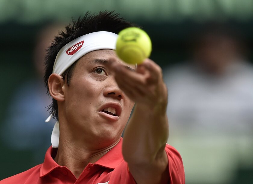 Kei Nishikori of Japan serves the ball to Dustin Brown from Germany during their second round match at the Gerry Weber Open ATP tennis tournament in Halle, Germany, Thursday, June 18, 2015. (AP Photo/Martin Meissner)