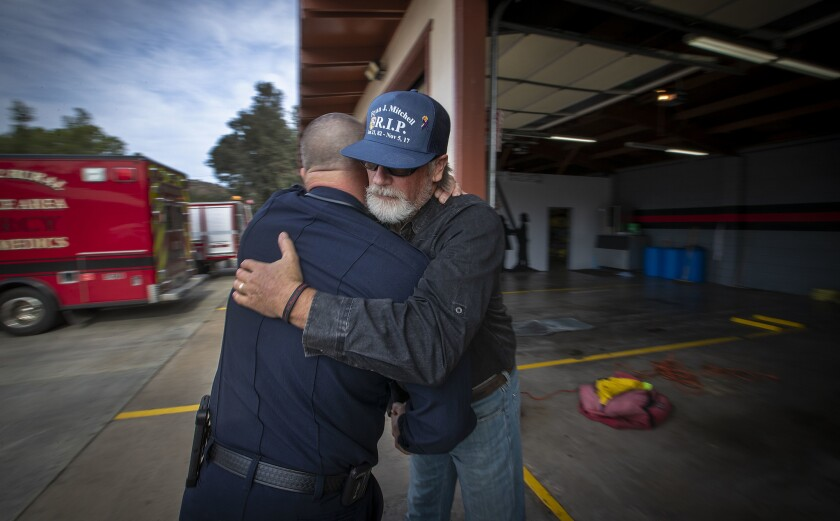 EL CAJON, CALIF. -- MONDAY, NOVEMBER 19, 2018: Ernie Marugg, Cal Fire Battalion Chief, left, hugs Wi
