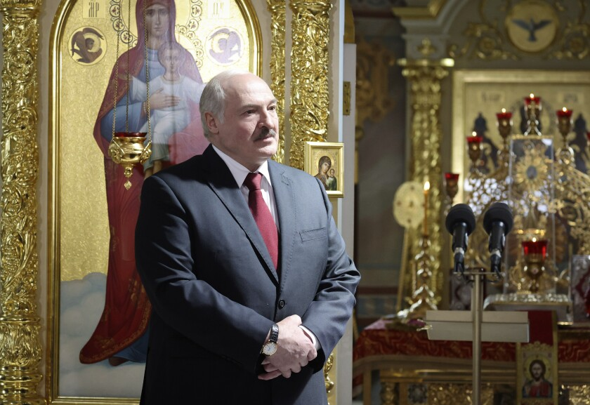 Belarusian President Alexander Lukashenko, left, attends the Orthodox Easter service in the town of Turov, some 270 km (167 miles) south of Minsk, Belarus, Sunday, May 2, 2021. (Maxim Guchek/BelTA Pool Photo via AP)