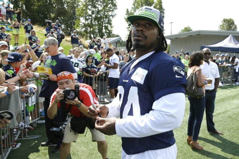 Seattle Seahawks running back Marshawn Lynch looks around while signing autographs for fans following NFL Football training camp, Friday, Aug. 1, 2014, in Renton, Wash. Friday was Lynch's first day attending training camp after staying away due to contract issues. (AP Photo/Ted S. Warren)