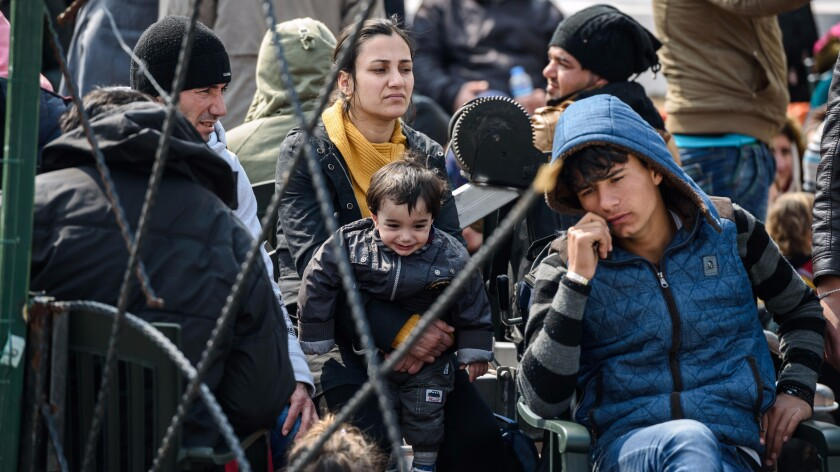 Migrants wait at a Turkish coast guard station at the Dikili district in Izmir on March 20, 2016, after they were caught trying to reach the Greek island of Lesbos from the Bademli village, western Turkey.