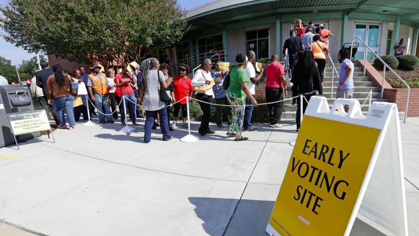 "Early voters line up in Raleigh, N.C. A fake advertisement spreading on social media encouraged voters to ""avoid the line"" and vote by texting. In response, Twitter released an official video along with its own tweet: ""Remember: You cannot vote via text or tweet."""