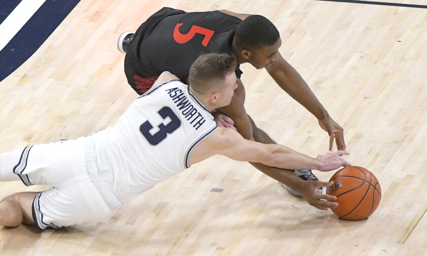 Aztecs guard Lamont Butler (5) and Utah State guard Steven Ashworth scramble for a loose ball during the first half Saturday.